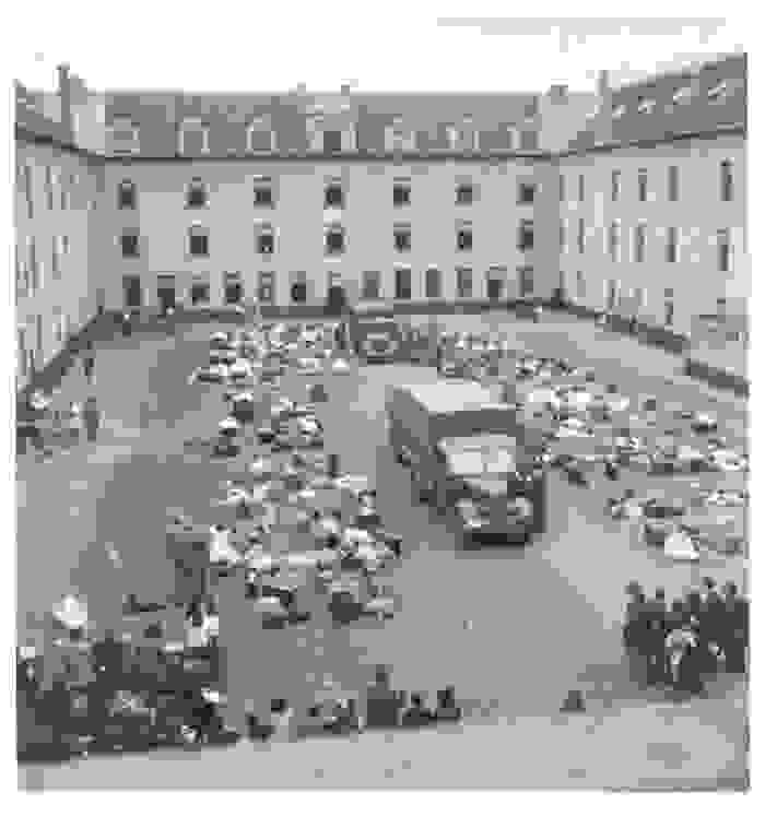 Possessions are stacked in the courtyard of the Dossin Barracks, there is a lorry in the centre of the courtyard
