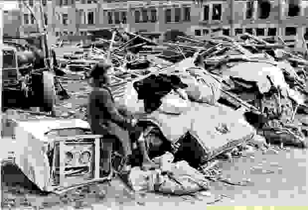 A woman is sitting on an appliance among the rubble after the bombing raid on Mortsel